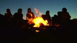 Photo of silhouettes of people sitting by Camp fire